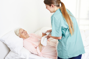 caregiver cleaning the hands of the senior woman