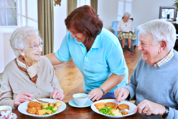 caregiver assists the two seniors in eating