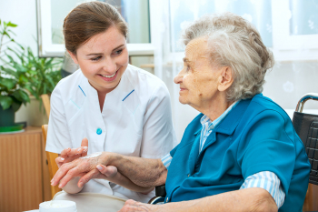 caregiver putting some cream on the hand of senior woman