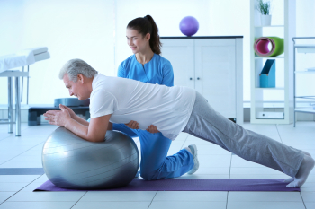 caregiver giving an assist to the senior in exercising