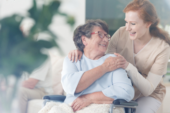 caregiver and senior woman smiling to each other